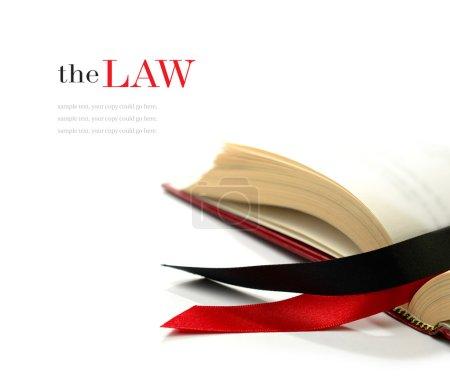 Photo pour Image stock du concept de droit. rubans de soie sur un livre juridique ouvert sur un fond blanc. espace copie. - image libre de droit