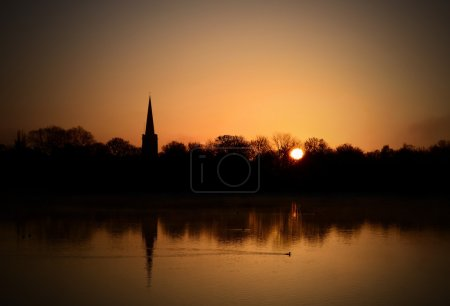Photo for Spring morning sunrise over English nature reserve with neighbouring village church. Copy space. - Royalty Free Image