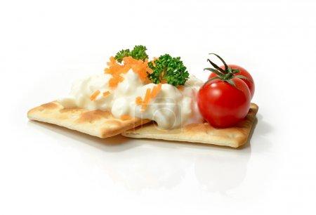 Photo pour Studio macro de tomates mûres avec fromage cottage faible en gras et les dés de carotte sur les craquelins croustillants. Espace de copie . - image libre de droit