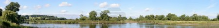 Photo for Panoramic image of the mouth of the River Dove at its confluence with the River Trent at Newton Solney, South Derbyshire, UK. The 45 mile river starts at Axe Edge Moor near Buxton and flows through the Peak District. - Royalty Free Image