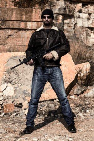 Photo pour Vue d'un homme avec une mitraillette en jeans et veste sur une carrière de Pierre. - image libre de droit