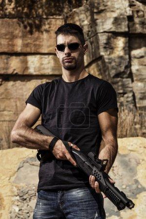 Photo pour Vue d'un homme avec un fusil de chasse en jeans et chemise noire sur une carrière de Pierre. - image libre de droit