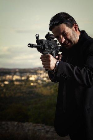 Photo pour Vue d'un agent tueur de type contractuel errant avec une veste longue et une mitrailleuse . - image libre de droit