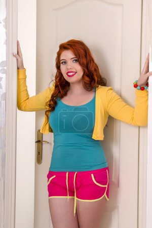 Photo pour Vue d'une belle rousse avec des vêtements colorés dans sa chambre . - image libre de droit