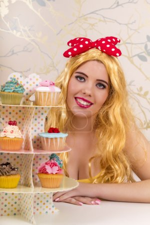 Beautiful pinup redhead girl with colorful cupcakes