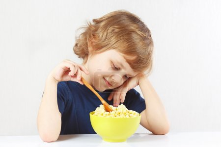 Photo for Little blonde child eating a millet porridge on white background - Royalty Free Image