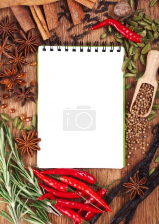 Photo for Open notebook with spices and herbs on the old wooden cutting board - Royalty Free Image