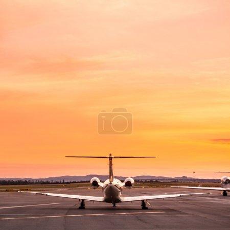 Photo pour Avion privé stationné à l'aéroport au coucher du soleil. - image libre de droit