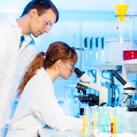 Photo pour Séduisante jeune femme chercheur et du superviseur masculin post doctorat en regardant la lame de microscope dans les sciences de la vie (forensics, microbiologie, biochimie, génétique, oncologie...) laboratoire - image libre de droit