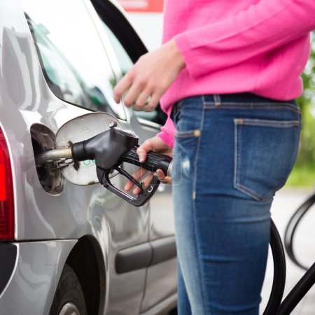Lady pumping gasoline fuel in car at gas station.