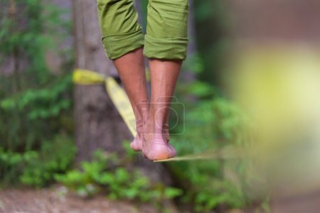 Photo for Slacklining is a practice in balance that typically uses nylon or polyester webbing tensioned between two anchor points. - Royalty Free Image