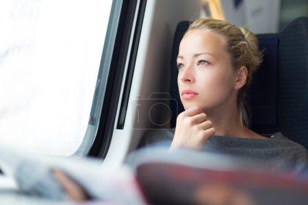 Photo pour Jeune dame réfléchie lisant tout en voyageant en train . - image libre de droit