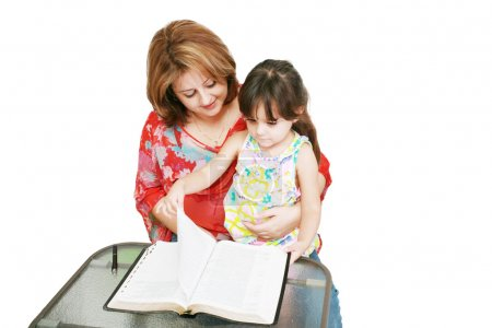 Minority woman and her daughter reading the Bible