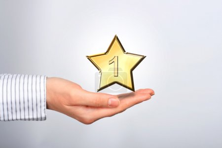 Photo pour Étoile d'or dans les mains. numéro un. - image libre de droit