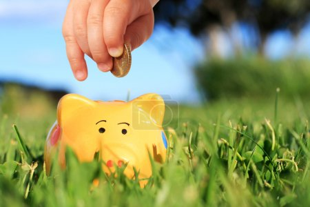 Photo for Baby hand and piggybank over nature background. - Royalty Free Image
