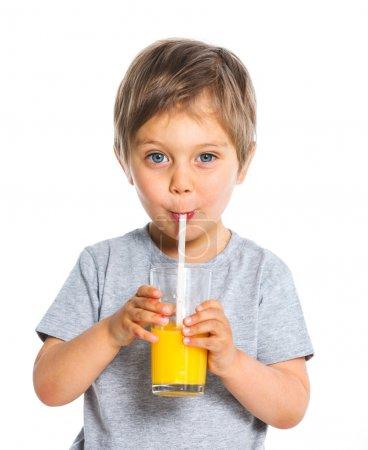 Photo pour Portrait de l'heureux petit garçon boire le jus d'orange. isolé sur fond blanc. - image libre de droit