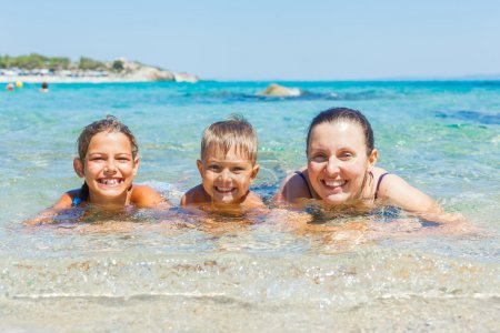 Photo pour Vacances famille - mère avec ses enfants s'amuser et baignade dans la mer transparente - image libre de droit