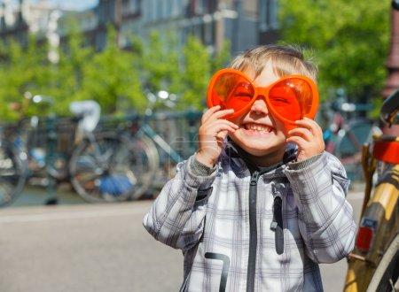 Photo pour Garçon marche dans des verres orange pour queensday néerlandaise sur la rue d'amsterdam - image libre de droit