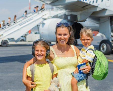 Photo pour Jeune maman avec deux enfants en face de l'avion - image libre de droit