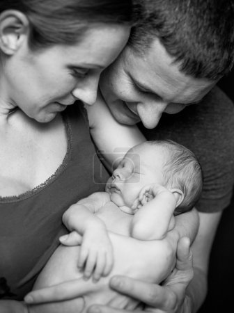 Photo pour Belle mère et père souriant tenant leur garçon nouveau-né - image libre de droit