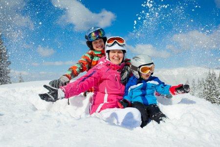 Photo pour Ski, hiver, familiale - souriant garçon à lunettes de ski et un casque avec sa mère et la sœur jouant dans la neige en station d'hiver - image libre de droit