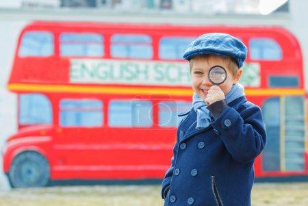 Photo pour Petit détective. Funny garçon regardant à travers la loupe près autobus scolaire anglais - image libre de droit