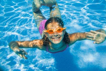 Photo pour La fille mignonne nageant sous l'eau et souriant - image libre de droit