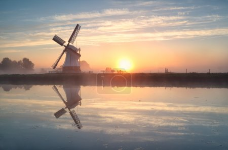 Dutch windmill reflected in river at sunrise