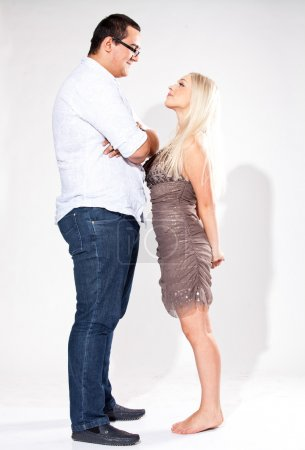 tall man looking down at small blond woman