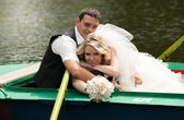 Newly married couple lying and hugging in rowing boat