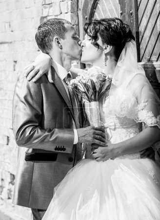 Closeup portrait of married couple kissing near old door