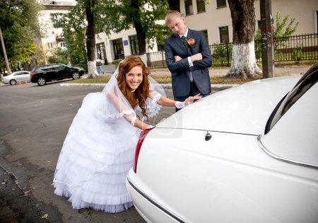 Bride pushing car while groom looking at her