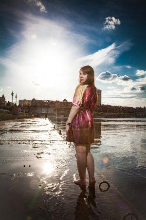 Woman in dress walking barefoot on embankment
