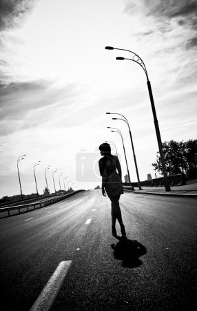 Silhouette photo of woman walking on empty highway