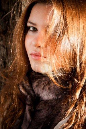 Photo pour Gros plan portrait de mignonne rousse fille posant dans la lumière du soleil - image libre de droit