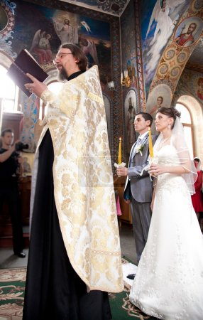Couple getting married in church by orthodox priest
