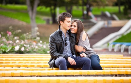 Photo for Beautiful dating couple hugging on yellow bench at park - Royalty Free Image