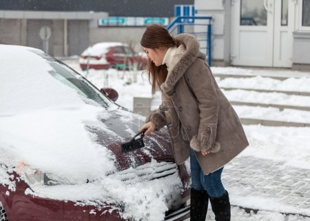 Woman cleaning her car after snow blizzard