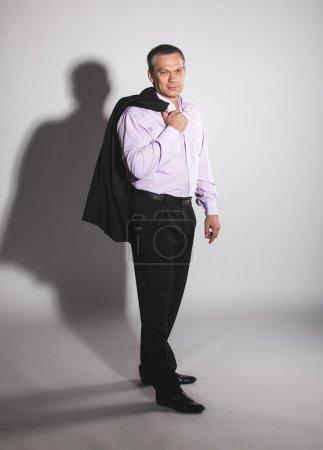 Portrait of elegant man in suit holding jacket over shoulder