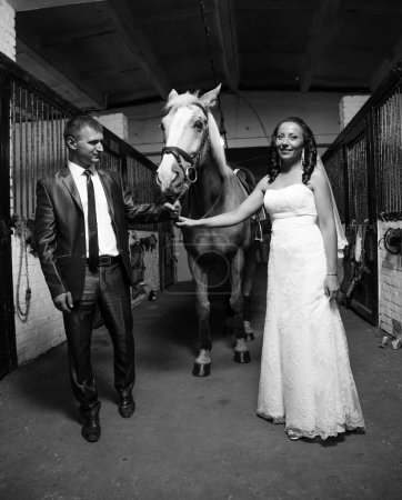 Photo of bride and groom holding horse by rein at stable