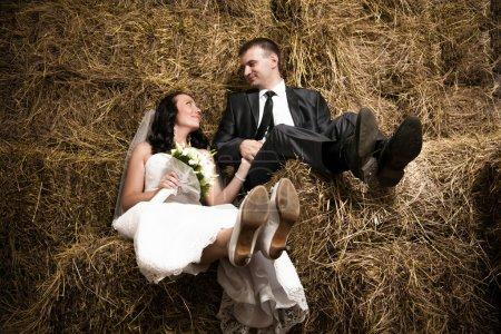 Photo pour Photo d'un couple marié tenant la main et assis sur du foin à l'écurie - image libre de droit