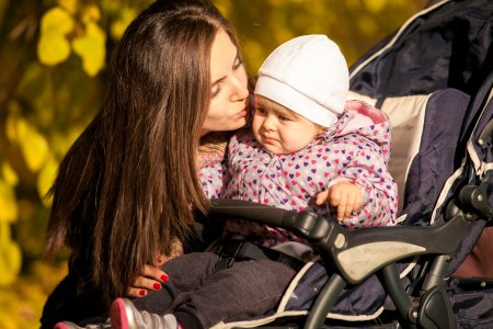 Portrait of mother kissing daughter in buggy