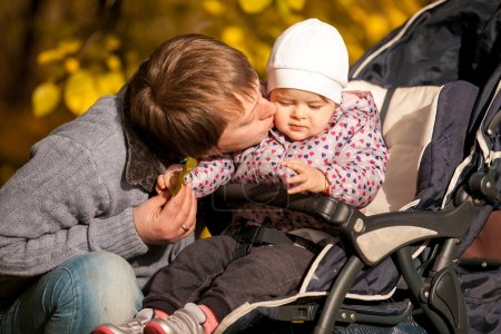 Father kissing daughter sitting in buggy at park