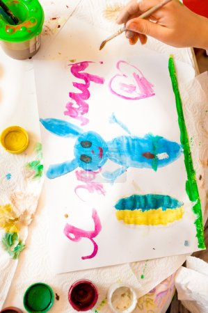 Shot of little girl drawing blue rabbit on canvas