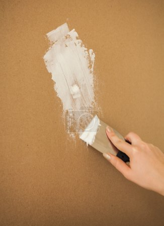 Closeup photo of hand working with spatula and pla...