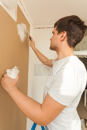 Portrait of young man aligning wall with putty