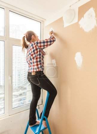 Woman working with putty and spatula on ladder