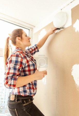 Portrait of young woman aligning gypsum cardboard