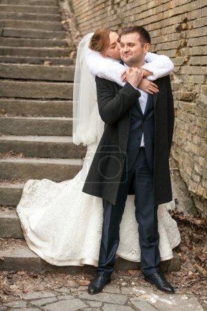 Photo pour Belle mariée câlin marié de retour sur les escaliers - image libre de droit