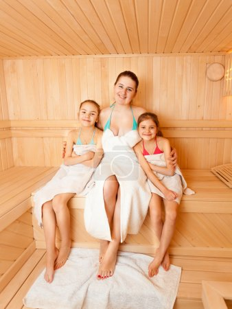 Daughters with mother sitting on bench at sauna